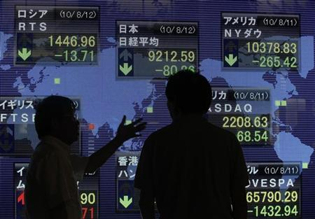 Men have a chat as they watch a board showing stock price index of Japan (C) and other countries outside a brokerage in Tokyo August 12, 2010. REUTERS/Kim Kyung-Hoon
