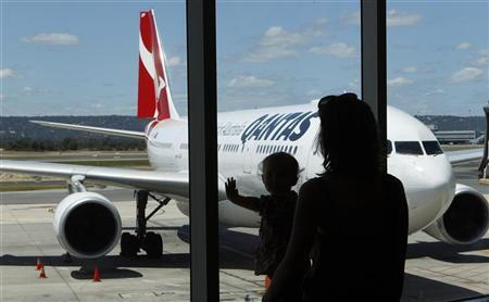 Stranded Qantas passengers look at a Qantas Airbus A330 plane as they wait for their flights at the departure gates of Perth Domestic Airport October 31, 2011. REUTERS/Daniel Munoz