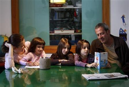Amelia Thomas (L) and Gonzalo Acha (R) sit with their daughters Beatriz, Leonor and Isabel at their home in Madrid, November 9, 2010. Gonzalo Acha and Amelia Thomas have eased into the roles the economic crisis has imposed on them: Acha as sole breadwinner with a salary frozen six years running, Thomas as what she calls ''creative homemaker''. They live with their three young daughters just blocks from Madrid's Puerta de Sol square where the ''los indignados'' (the indignant) protesting against government spending cuts have regularly gathered. So far, Gonzalo and Amelia have not joined.       REUTERS/Andrea Comas/Files