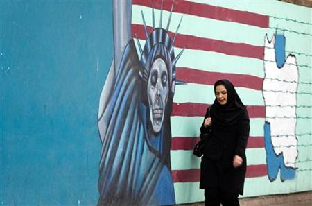 EDITORS' NOTE: Reuters and other foreign media are subject to Iranian restrictions on their ability to film or take pictures in Tehran.A woman walks past an anti U.S. mural at the former U.S. embassy in Tehran November 19, 2011. The former U.S. embassy was the site of the 1979-1981 hostage crisis in which a group of militant Iranian students held 52 U.S. diplomats hostage for 444 days. The building is currently being used by the Iranian Revolutionary Guards. REUTERS/Raheb Homavandi  (IRAN - Tags: POLITICS CIVIL UNREST)