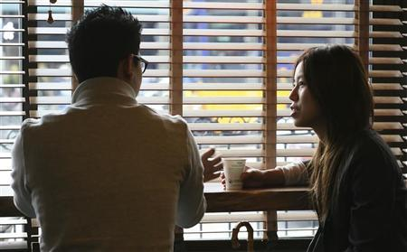 Phil Hong (left) and Alice Yu (right) drink coffee at a Starbucks store at 1st and Pike in Seattle, Washington, March 25, 2010. REUTERS/Marcus Donner