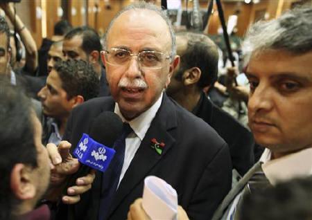 Libya's Prime Minister designate Abdurrahim El-Keib (C) talks to the media in Tripoli November 22, 2011. REUTERS/Mohammed Salem