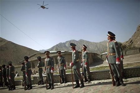 Afghan honor guards watch an Afghan helicopter fly over the security handover ceremony in Panjshir province, July 24, 2011.REUTERS/Ahmad Masood