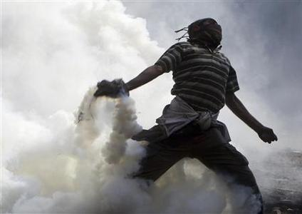 A protester throws a tear gas canister, which was earlier thrown by riot police during clashes along a road which leads to the Interior Ministry, near Tahrir Square in Cairo November 22, 2011. REUTERS/Amr Abdallah Dalsh
