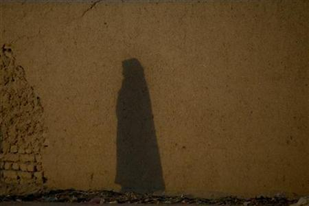 The shadow of an Afghan woman wearing a burqa is seen on a mud wall as she walks down a street in Quetta November 21, 2011. REUTERS/Naseer Ahmed