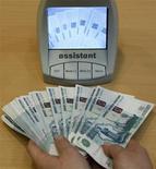 Сотрудница банка в Санкт-Петербурге проверяет деньги, 4 февраля 2010 года. Рубль снизился в начале торгов среды к бивалютной корзине и доллару США на фоне глобального неприятия риска из-за опасений инвесторов в отношении роста мировой экономики. REUTERS/Alexander Demianchuk