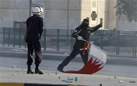 A policeman confronts a protester in the Shi'ite village Sanabis near Manama February 14, 2011.  REUTERS/Hamad I Mohammed