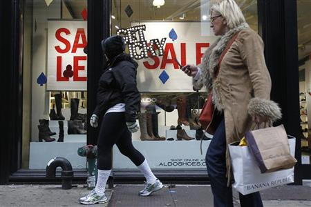A shoppers walks past a sale sign hanging in a storefront in New York November 22, 2011. REUTERS/Jessica Rinaldi