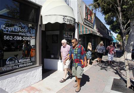 People walk past shops at the downtown area in Seal Beach, California October 13, 2011.    REUTERS/Alex Gallardo
