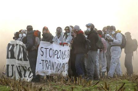 Anti-nuclear demonstrators hold a banner ''stop nuclear waste train'' in a field in Lieusaint near Valognes November 23, 2011 as they try to enter on the tracks before the departure of the train convoy of CASTOR containers which carry radioactive nuclear waste. REUTERS/Benoit Tessier