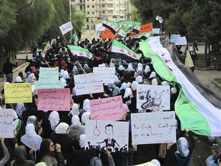 Demonstrators march against Syria's President Bashar al-Assad in Homs November 21, 2011. Banners read, (C) ''Freedom for detained students at Assad's prisons''. Picture taken November 21, 2011.    REUTERS/Handout
