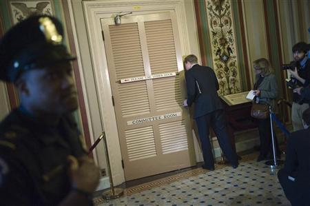 An aide peeks in the committee room door as Democratic members of the 'super committee' wrap up a meeting at the U.S. Capitol in Washington November 16, 2011. REUTERS/Jonathan Ernst