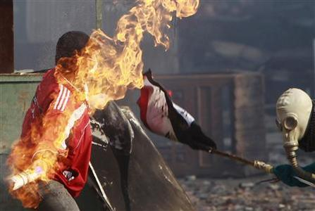 A protester throws a Molotov cocktail (petrol bomb) at riot police during clashes along a road which leads to the Interior Ministry, near Tahrir Square in Cairo November 23, 2011.  REUTERS/Amr Abdallah Dalsh