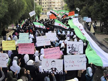 Demonstrators march against Syria's President Bashar al-Assad in Homs November 21, 2011. The banners (C) read ''Freedom for detained students at Assad's prisons''. Picture taken November 21, 2011.    REUTERS/Handout