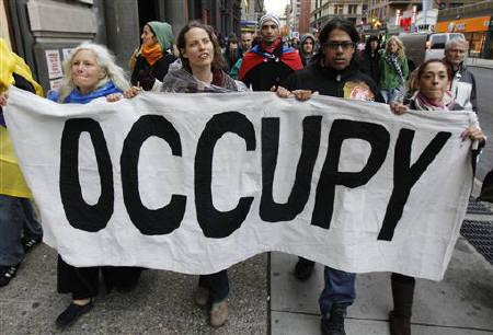 Occupy Wall Street demonstrators march while carrying a banner during what protest organizers called a ''Day of Action'' in New York November 17, 2011. REUTERS/Jessica Rinaldi