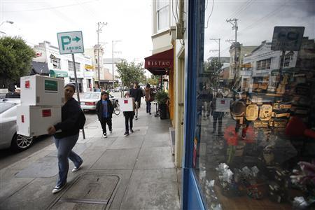 People carrying boxes walk past Chocolate Covered candy shop in the Noe Valley district in San Francisco, California November 21, 2011.  REUTERS/Stephen Lam