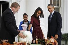 <p>U.S. President Barack Obama (R) watches as his daughter Malia pets the 2011 Thanksgiving Turkey, Liberty, alongside her sister Sasha, during a ceremony on the North Portico of the White House in Washington November 23, 2011. REUTERS/Jason Reed</p>