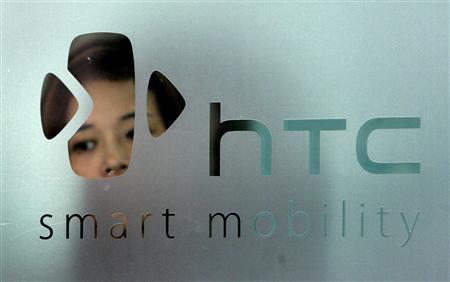 A woman stands behind a logo of HTC in Taipei in this September 24, 2008 file photo.  REUTERS/Pichi Chuang/Files