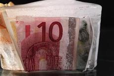 Замороженные евро банкноты в Скопье, 17 ноября 2011 года. Евро торгуется недалеко от минимума семи недель в четверг, слегка корректируясь после сильного снижения из-за слабого размещения Германией своих 10-летних долговых бумаг в среду, что усилило страхи инвесторов о том, что долговой кризис еврозоны начал поглощать крупнейшую экономику еврозоны. REUTERS/Ognen Teofilovski