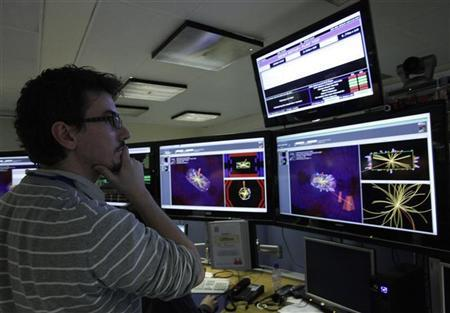 A scientist looks at the first collisions pictures at full power at the Compact Muon Solenoid (CMS) experience control room at the Large European Organisation for Nuclear Research (CERN) in Meyrin, near Geneva March 30, 2010.     REUTERS/Denis Balibouse