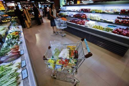 A trolley laden with fresh and processed food sits parked in an aisle as customers shop at a supermarket in Mumbai May 30, 2011. REUTERS/Vivek Prakash/Files