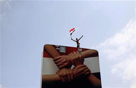 An anti-government protester waves Yemen's national flag as he stands on a billboard during a demonstration to demand the ouster of President Ali Abdullah Saleh in the southern city of Taiz November 10, 2011. REUTERS/Khaled Abdullah