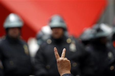 An Occupy Wall street protestor gestures in front of New York City Police inside Zuccotti Park as protests moved through the streets of lower Manhattan near the New York Stock Exchange during what organizers called a ''Day of Action'' in New York, November 17, 2011.  REUTERS/Mike Segar