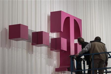 Workers inspect the logo of the Deutsche Telekom at the CeBIT computer fair in Hanover February 27, 2011.  REUTERS/Tobias Schwarz