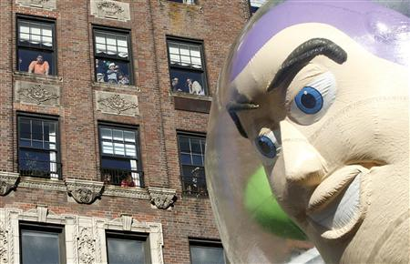 People look out their apartment windows as the Buzz Lightyear balloon floats down Central Park West during the 85th Macy's Thanksgiving day parade in New York November 24, 2011.    REUTERS-Gary Hershorn