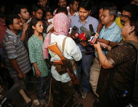 Maoist leader Kishenji (C, facing back) speaks to the media in Bholagara village of West Bengal October 22, 2009. REUTERS/Jayanta Shaw/Files