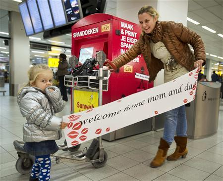Two-year-old Luna (L) and her aunt hold a banner at Amsterdam Airport Schiphol November 24, 2011. REUTERS/Paul Vreeker/United Photos