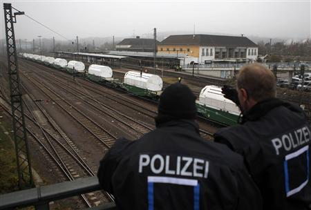 German police observe the train transporting Castor containers with radioactive waste, during a stop in Neunkirchen near Saarbruecken November 25, 2011.   REUTERS/Alex Domanski