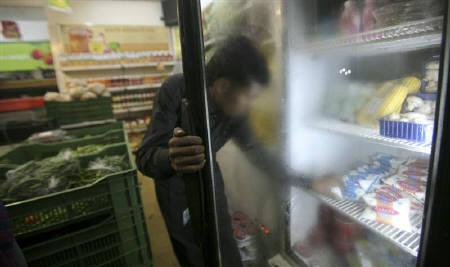 A man takes out a packet of yogurt from a refrigerator at a food store in Noida on the outskirts of New Delhi November 24, 2011. REUTERS/Parivartan Sharma