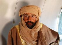 Сын Муаммара Каддафи Саиф аль-Ислам в самолете по дороге в Зинтан 19 ноября 2011 года. Захваченному в плен бойцами новых ливийских властей сыну Муаммара Каддафи Саифу аль-Исламу необходима операция по ампутации пальцев, пораженных гангреной, сообщил Рейтер осмотревший пленника врач. REUTERS/Ismail Zitouny