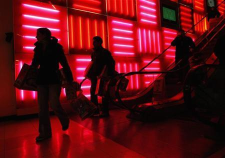 Customers take the escalator as they shop at a store in New York November 24, 2011.  REUTERS/Eric Thayer