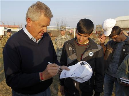 Colin Montgomerie (L) of Scotland autographs a golf cap for an Afghan boy after golf training in Kabul November 25, 2011. REUTERS/Omar Sobhani