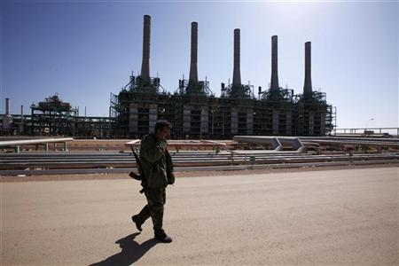 An armed National Transitional Council (NTC) fighter patrols inside the Libyan Oil Refining Company (LERCO) in Ras Lanuf, about 660 km (410 miles) west of Tripoli, November 5, 2011. REUTERS/Youssef Boudlal