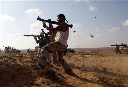 Anti-Gaddafi fighters hold RPGs during a firefight against Gaddafi loyalists in a village near Sirte, one of Muammar Gaddafi's last remaining strongholds September 17, 2011.    REUTERS/Goran Tomasevic