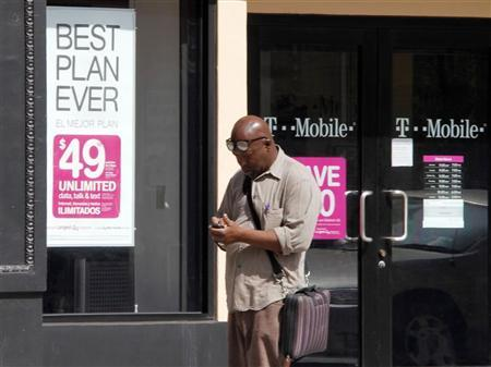 A man checks his mobile phone as he walks past a T-Mobile store in downtown Los Angeles, California August 31, 2011.     REUTERS/Fred Prouser