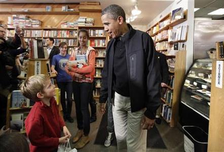 U.S. President Barack Obama talks to Alexander Mussehl, 5 year-old, as his daughter Malia (L) smiles at Kramerbooks in Washington, November 26, 2011. REUTERS/Yuri Gripas