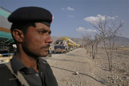 A policeman stands guard near trucks, some of which were carrying supplies to NATO forces in Afghanistan, as they line up in the outskirts of Quetta after the Chaman border crossing was closed to traffic November 26, 2011.  REUTERS/Naseer Ahmed