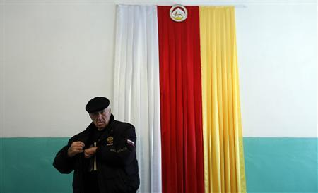 A man walks past a South Ossetian flag on the wall during a visit to a polling station to cast his vote in the South Ossetian city of Tskhinvali November 27, 2011. The breakaway Georgian region of South Ossetia votes in the second round of presidential elections on Sunday.  REUTERS/Eduard Korniyenko