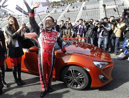 Toyota Motor Corporation President and Chief Executive Akio Toyoda poses next to a production prototype of the '86' compact rear-wheel drive sports car during its unveiling at Fuji Speedway in Oyama, central Japan, November 27, 2011.  REUTERS/Kim Kyung-Hoon