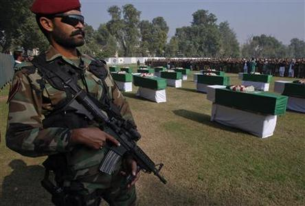 An army soldier stands guard near caskets of soldiers killed in a cross-border attack along Pakistan and Afghan during their funeral prayers in Peshawar November 27, 2011. Pakistan on Sunday buried 24 troops killed in a NATO cross-border air raid that has pushed a crisis in relations with the United States towards rupture.  REUTERS-Stringer