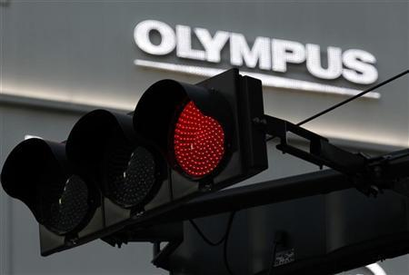 A logo of Olympus Corp is seen behind a traffic signal outside of an electronic shop in Tokyo November 17, 2011.  REUTERS/Kim Kyung-Hoon