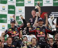 Dupla de pilotos da Red Bull Sebastian Vettel e Mark Webber comemora com integrantes da equipe Red Bull após o GP Brasil de Fórmula 1, em Interlagos. 27/11/2011 REUTERS/Nacho Doce
