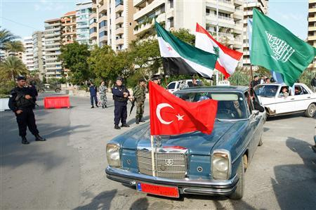 Turkish, Syrian, Lebanese and Saudi Arabian flags flutter atop a car driving past Lebanese policeman and army soldiers during a mass rally organized by the Future Movement in the northern city of Tripoli, November 27, 2011. REUTERS/ Omar Ibrahim