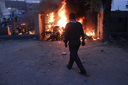A man walks past burning motorbikes which were set ablaze by an angry mob in Karachi November 27, 2011.  REUTERS/Athar Hussain