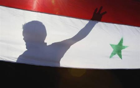 A Syrian protester is silhouetted behind a Syrian flag during a demonstration against President Bashar Al-Assad in front of the Syrian embassy in Amman May 22, 2011. REUTERS/Majed Jaber/Files