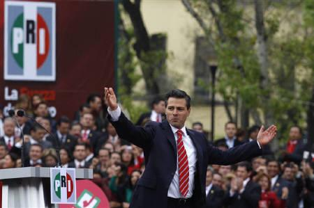Enrique Pena Nieto, former Mexico state governor and a presidential candidate for the Institutional Revolutionary Party (PRI), gestures on stage to his supporters after filing for candidacy for his party in Mexico City November 27, 2011. REUTERS/Carlos Jasso
